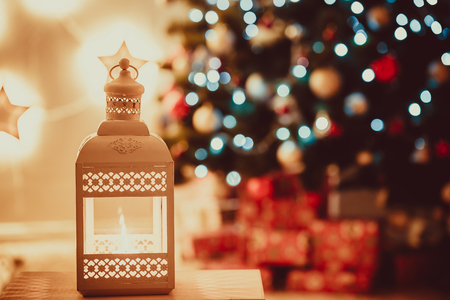 Close-up of Christmas lantern with burning candles on blurred background living room with Christmas tree.