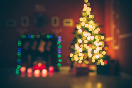 hearthside: Beautiful  Defocused background new year room with decorated Christmas tree, gifts and fireplace with the glowing lights at night. The idea for postcards. Soft focus. Shallow DOF Stock Photo