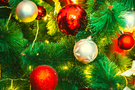 mantel: Beautiful decorated Christmas tree with red and goldish baubles and garland, in the new-year background. The idea for postcards. Soft focus. Shallow DOF Stock Photo