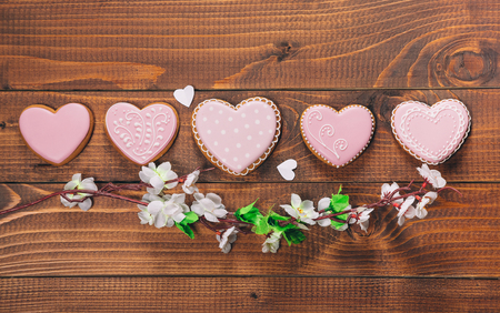 spicecake: Heart-shaped biscuits and flowers for Valentines Day. Gingerbread Valentine on wooden background. Free space for your text