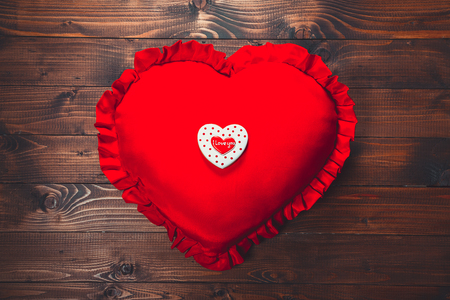spicecake: Heart-shaped biscuits on red pillow, for Valentines Day. Gingerbread Valentine on wooden background. Free space for your text