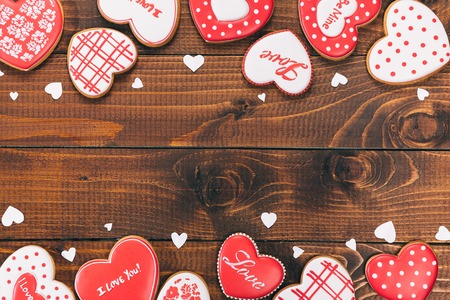 Heart-shaped biscuits for Valentines Day. Framework with Gingerbread Valentine on wooden background Stock Photo