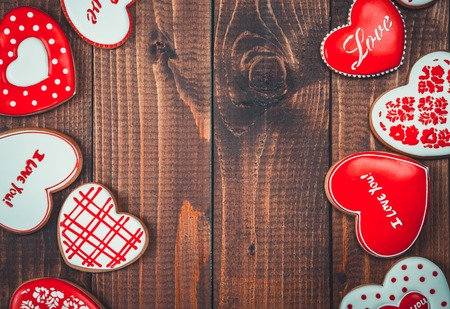spicecake: Heart-shaped biscuits for Valentines Day. Framework with Gingerbread Valentine on wooden background Stock Photo