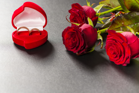 Beautiful red roses bouquet and wedding rings on a black background. Postcard for Valentine day or Wedding. Free space for text