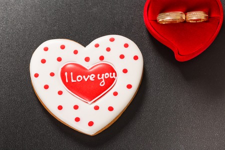 uprzejmości: Beautiful gingerbread heart and wedding rings on a black background. Postcard for Valentine day or Wedding. Free space for text