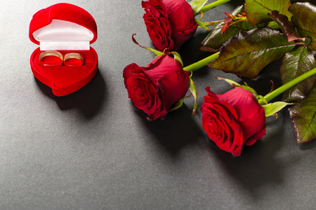 uprzejmości: Beautiful red roses bouquet and wedding rings on a black background. Postcard for Valentine day or Wedding. Free space for text