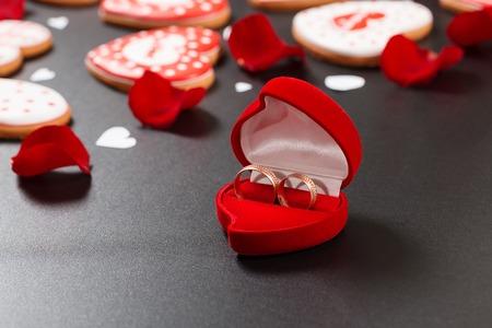 Piękne czerwone róże płatków i obrączki na czarnym tle. Pocztówka na Walentynki lub Ślub. Wolne miejsce na tekst