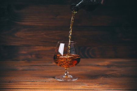 snifter: Pouring brandy or cognac from the bottle into the glass against wooden background