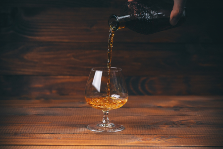 Pouring brandy or cognac from the bottle into the glass against wooden background