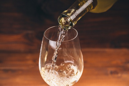 Pouring white wine from a bottle in a close up view of the wineglasses against wooden background Stock Photo