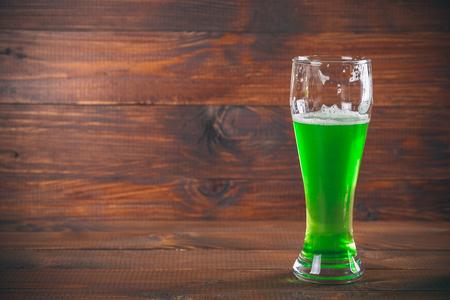 St Patricks Day concept mug green beer against wooden background