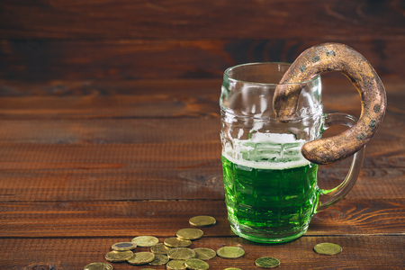 Beautiful background for St. Patricks day with a glass of green beer, gold coins and a horseshoe on a wooden table. Free space