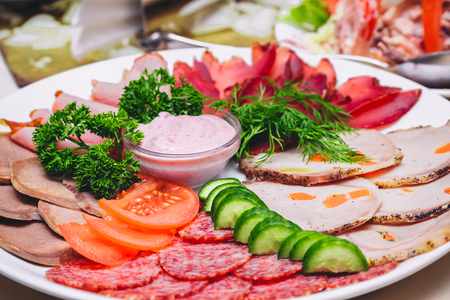 cold cut: Beautiful meat and sausage sliced on a white plate on a festive table