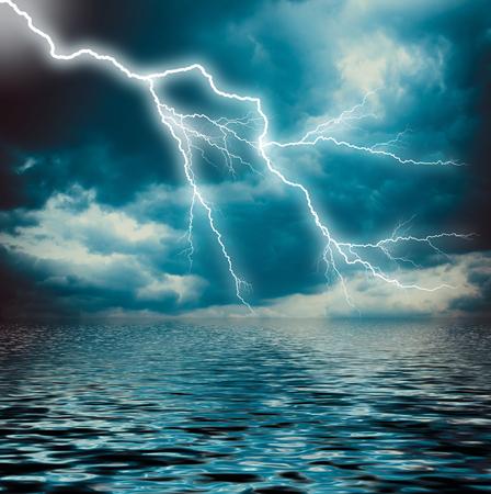 thunderhead: Lightning strike on the dark cloudy sky over the sea Stock Photo