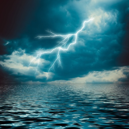 Lightning strike on the dark cloudy sky over the sea Stock Photo
