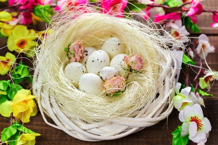 Beautiful Easter eggs in nest with flowers on the wooden background