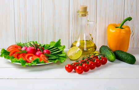 Cucumbers, radish, tomatoes cherry, olive oil, herb and spices on old white wooden background. Set for healthy foods. Ingredients for salad. Stock Photo