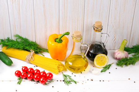 Spaghetti, tomatoes cherry, olive oil, herb and spices on old white wooden background. Set for healthy foods. Ingredients for salad.