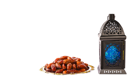 Beautiful a shining Fanus lantern and dried dates on a silver tray isolation on white background. The Muslim feast of the holy month of Ramadan Kareem. Free space for your text
