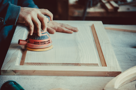 Close-up of carpenter using sander for wood furniture. Soft focus. Shallow DOF.