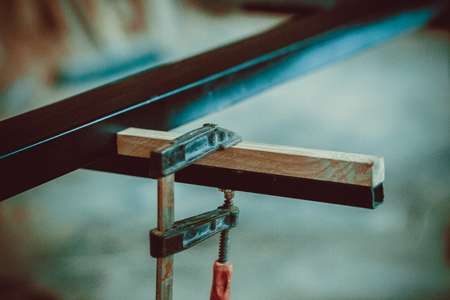 Craftsman using clamps fixate two pieces of wood and iron. The process of making desk, furniture. Soft focus. Shallow DOF.