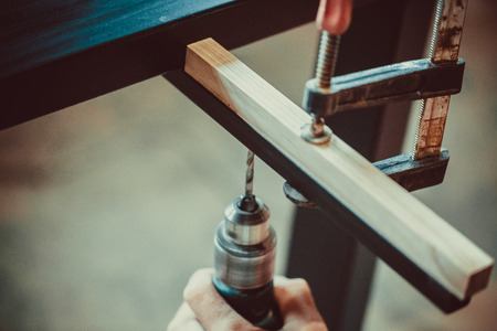 makes: Man using the drill makes a hole in wood and iron strap. The process of making desk, furniture. Soft focus. Shallow DOF.