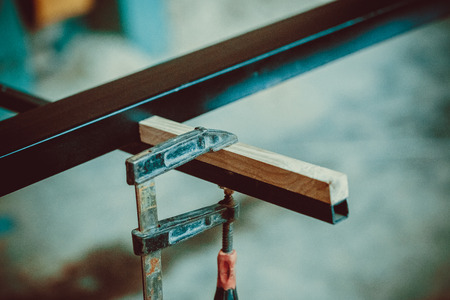fixate: Craftsman using clamps fixate two pieces of wood and iron. The process of making desk, furniture