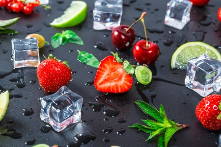 Summers freshest fruit and berries currants, gooseberries, cherries, limes, strawberries and fresh mint leaves on a black background Stock Photo