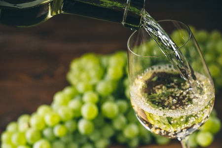White wine poured into a glass with a bunch of green grapes against wooden background