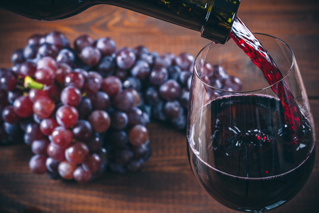 Pouring red wine into the glass with a bunch of red grapes against wooden background Stock Photo
