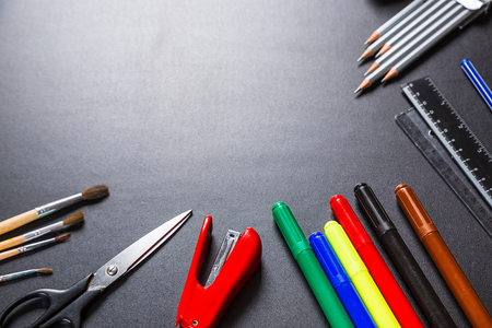 Old blackboard with chalk, stapler, scissors, pencils and stationery. A beautiful backdrop for education, a free space for your text Stock Photo