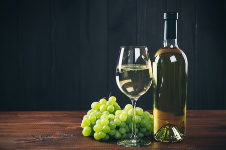 Beautiful white wine in wine glass with a bunch of green grapes against wooden background with free space Stock Photo