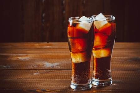 Beautiful cold fizzy cola soda with cubes ice in glasses goblet on old wooden background with free space.