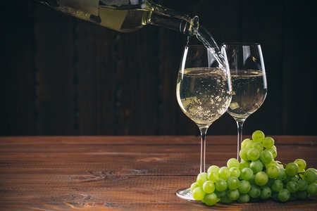 Pouring white wine from the bottle into a glass with a bunch of green grapes against wooden background with free space Stock Photo