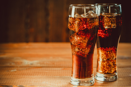 Beautiful cold fizzy cola soda with cubes ice in glasses goblet on old wooden background