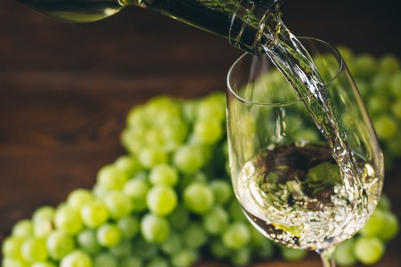 Pouring white wine into a glass with a bunch of green grapes against wooden background Stock Photo