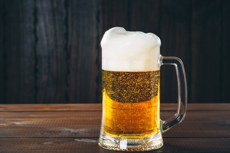 Mug of beer on the wooden background. Beautiful background of the Oktoberfest
