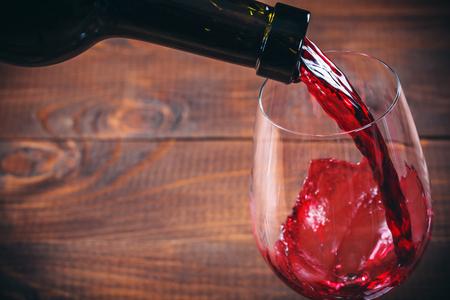 Verter el vino tinto en el vaso sobre fondo de madera Foto de archivo