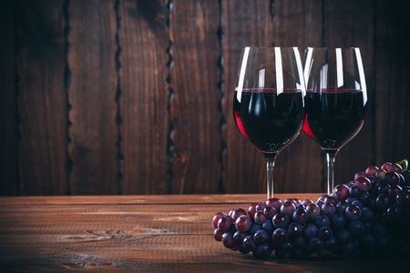 Two wine glass of red wine and grape on wooden background.