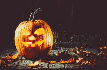 Halloween-Kürbis mit leuchtendem Gesicht auf einem hölzernen Hintergrund in einer gespenstischen Waldnacht