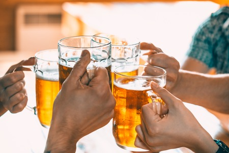 Happy Friends Drinking Beer And Clinking Glasses At Pub