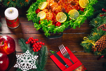Beautiful Christmas table dinner time with roasted meats, candles and New Year décor. Background thanksgiving. The concept of a family holiday, delicious food
