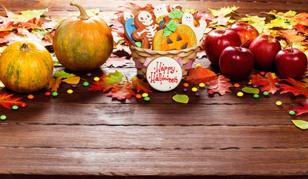 Beautiful festive background for Halloween with basket gingerbread, autumn leaves, berries and candy on a wooden table. Stock Photo