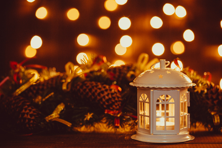 Christmas lantern with burning candles and garland on vintage wooden table with golden bokeh. Free space
