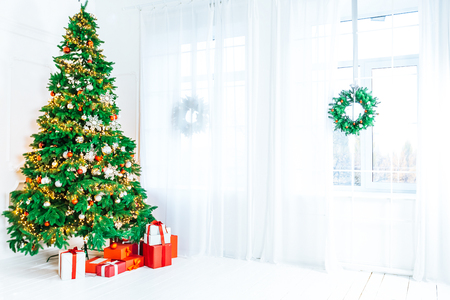 Christmas living room with a Christmas tree, gifts and a large window. Beautiful New Year decorated classic home interior