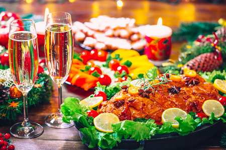 Christmas table dinner time with roasted meats decorated in Christmas style with glasses champagne. Background thanksgiving. The concept of a family holiday, delicious food.