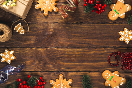 Christmas background with gifts, toys, tree branches, New Year decor, candies, and gingerbread cookies on old wooden background. Frame with free space. Merry Christmas greeting card Stock Photo