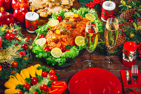 Christmas table dinner time with roasted meats, candles and New Year décor. Background thanksgiving. The concept of a family holiday, Beautiful delicious food