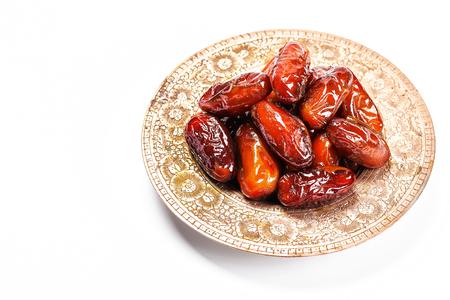 干枣放在传统托盘上,白色背景。斋月Kareem