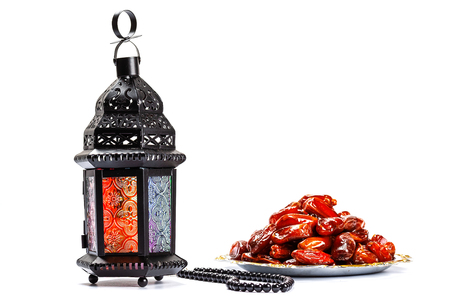 The Muslim feast of the holy month of Ramadan Kareem. Beautiful background with a shining lantern Fanus and dried dates on white. Free space for your text 免版税图像
